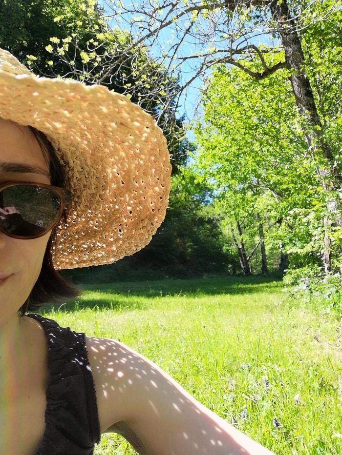 woman in straw hat sitting in grassy area